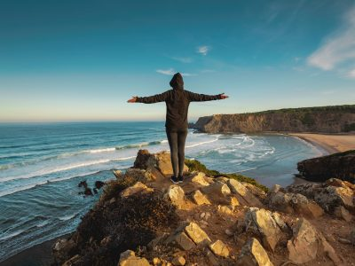 Woman looking to the ocean with arms wide open