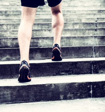Man runner running on stairs in city, sport training. Young male jogger athlete training and doing workout outdoors in city. Fitness and exercising outdoors urban environment.